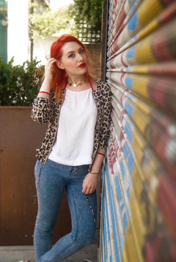 Red haired girl wears leopard print bomber jacket next to street art graffiti