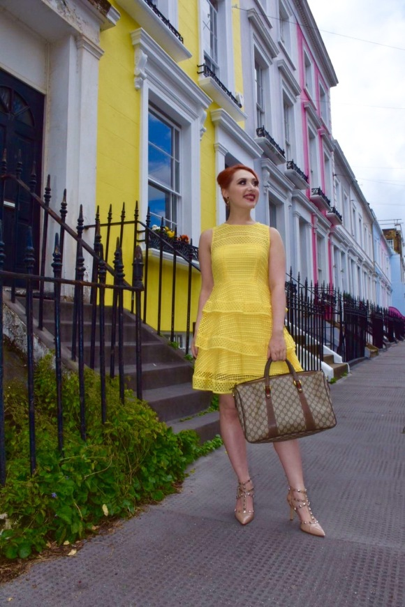 Alice Cruickshank blogger wearing yellow lace dress in Notting Hill next to colourful houses
